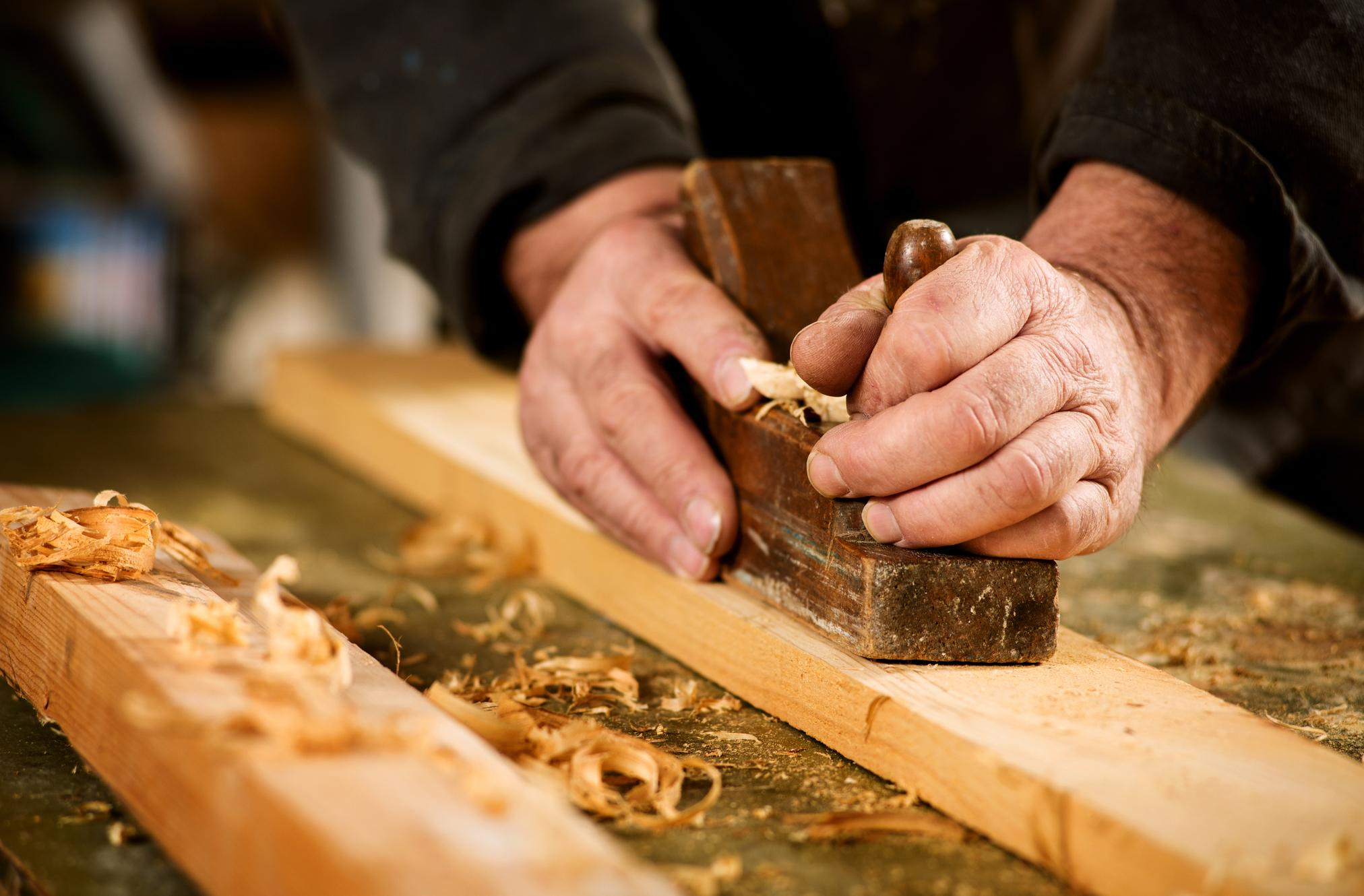 Carpenter using tools to smooth and level wood